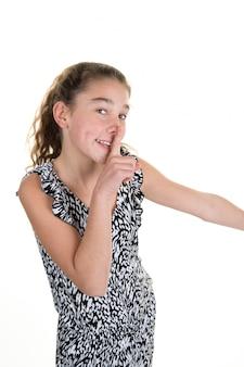 La ragazza graziosa che mette il dito fino alle labbra e chiede il silenzio