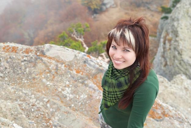 Bella ragazza sulla roccia con la nebbia