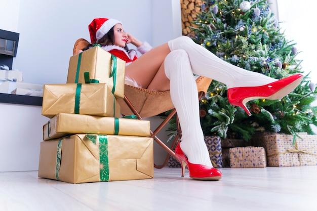 La ragazza graziosa si siede su una sedia vicino all'albero di natale festivo, molti regali sul pavimento, mattina di natale. una grande montagna di regali di natale avvolti in carta oro giallo e nastro verde.