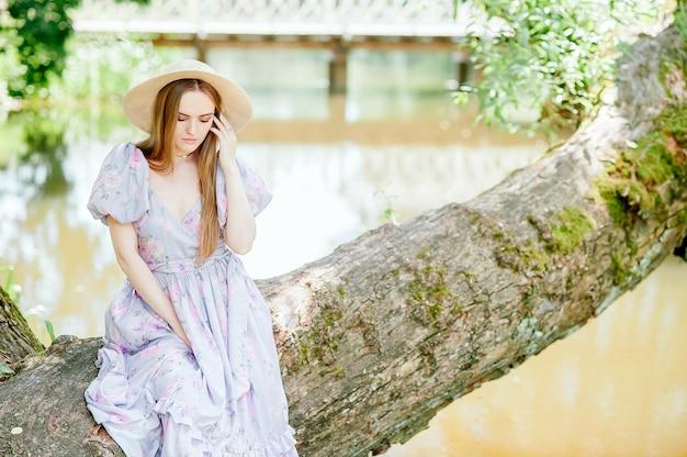 Una bella ragazza si siede sul bordo di un albero vicino al fiume e distoglie lo sguardo