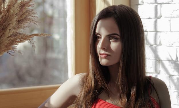 Ragazza graziosa che si siede accanto alla finestra che gode della luce solare