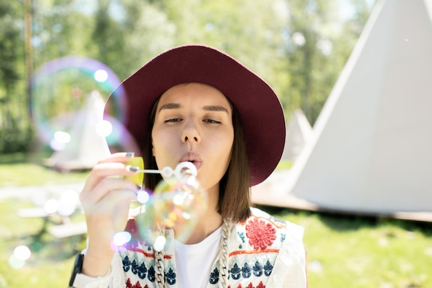Bella ragazza in piedi contro le tende da campeggio e soffiando bolle di sapone divertendosi all'aperto
