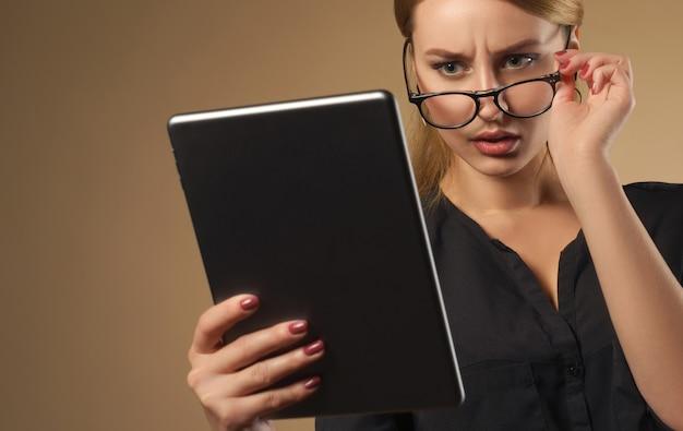 Bella ragazza che prende gli occhiali e guarda il tablet con la faccia confusa