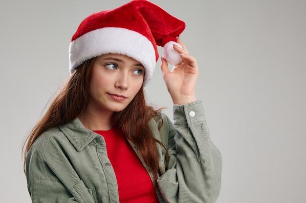 Bella ragazza toccando pom-pom sulla festa di capodanno natale cappello rosso