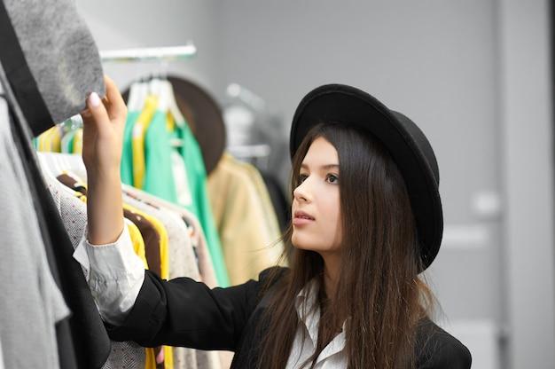 Bella ragazza che prova i cappelli neri alla moda e moderni nel negozio di abbigliamento. in piedi vicino a vestiti colorati appesi alle grucce. sentirsi bene, sembrare positivo, soddisfatto. indossare camicia classica bianca, cardigan.