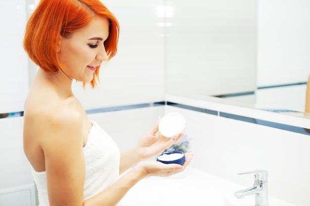 Pretty girl utilizzare prodotti per la cura in un bagno luminoso.