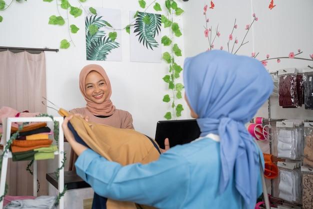 Una bella ragazza con il velo riceve da un cliente dei vestiti che verranno comprati e pagati al...