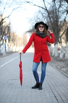 Bella ragazza in una passeggiata con l'ombrello rosso in città