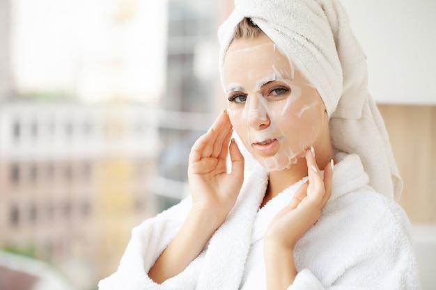 Bella ragazza che indossa la maschera per la cura del viso a casa.