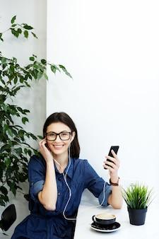 Bella ragazza con i capelli neri che indossa camicia blu spogliata e occhiali seduti in un caffè con il telefono cellulare e la tazza di caffè, concetto di freelance, ritratto, ascolto di musica.