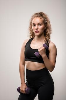 Bella ragazza con capelli ricci biondi che tiene i manubri nelle mani mentre si fa esercizio per i muscoli delle braccia durante l'allenamento