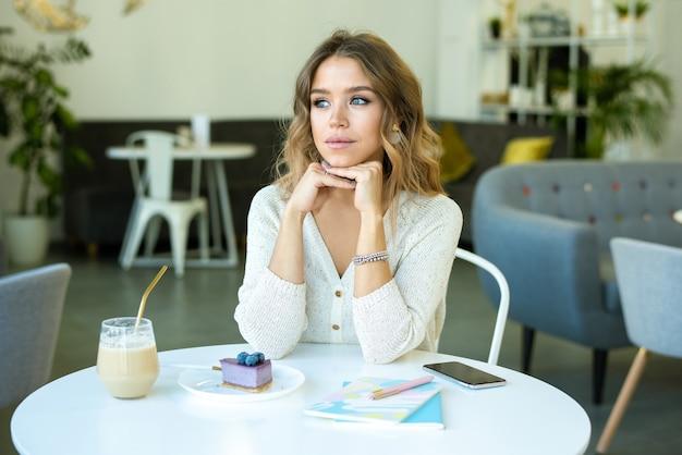 Bella ragazza con capelli ondulati biondi pensando a qualcosa mentre è seduto al tavolo in caffè, avendo cappuccino e cheesecake