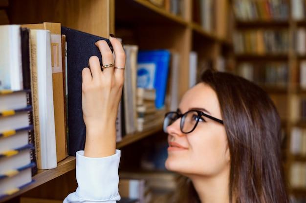 Bella ragazza con i capelli scuri con gli occhiali che cerca il libro giusto