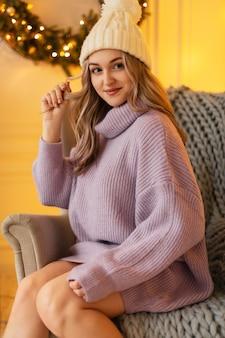 Bella ragazza con un cappello alla moda e un maglione lavorato a maglia vintage si siede su una sedia con un plaid sullo sfondo di decorazioni natalizie e luci gialle a casa