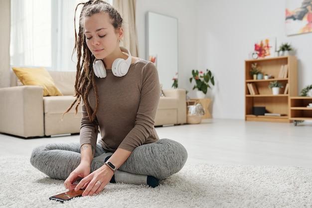 Bella ragazza con le cuffie che si siede con le gambe incrociate sul pavimento mentre ascolterai l'audio di yoga nello smartphone