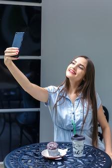 Bella ragazza con i capelli lunghi fa selfie per telefono, seduto in un caffè all'aperto