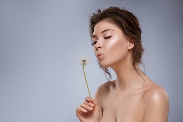 Bella ragazza con trucco nudo che soffia il dente di leone isolato su grigio