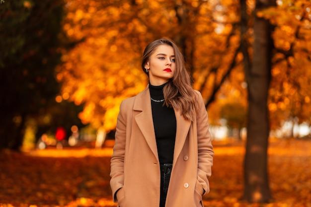 Bella ragazza con le labbra rosse in un cappotto alla moda con un maglione vintage nero cammina in un fantastico parco autunnale con fogliame arancione al tramonto