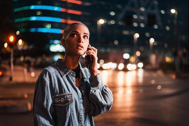 Bella ragazza con vestiti alla moda che tiene smartphone all'aperto la sera, città illuminata