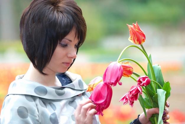 Bella ragazza con i tulipani con uno sfondo morbido