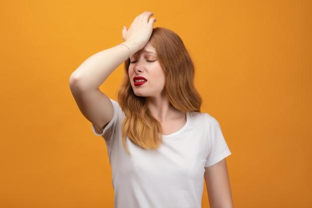 Bella ragazza con i capelli rossi ondulati, che indossa la maglietta bianca ha commesso un errore, incerta con dubbio, pensando con la mano sulla testa. concetto pensieroso. isolato su sfondo giallo