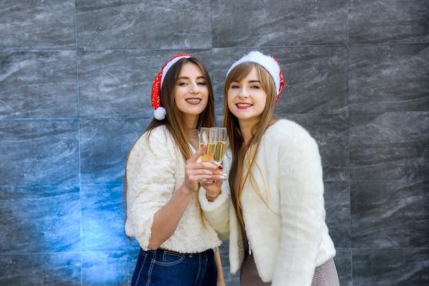 Belle ragazze con bicchieri di champagne che celebrano il nuovo anno. due donne brune in giacche di pelliccia