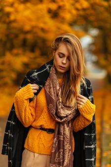 Piuttosto splendida giovane donna con cappello di paglia vintage in eleganti abiti estivi in sandali con tacco estivi alla moda in posa vicino a un edificio moderno nero in città. modello di moda ragazza carina sulla strada. sguardo giovanile.