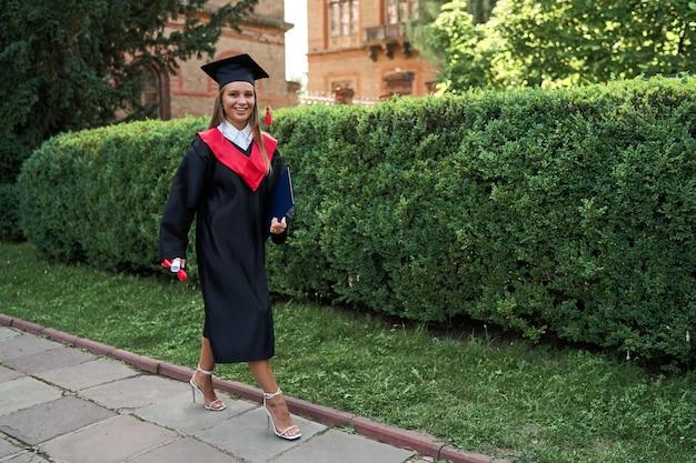 Bella ragazza laureata in abito di graduazioni che cammina con il diploma nel campus.