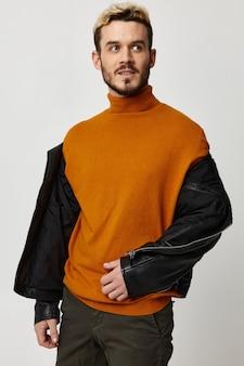 Bel ragazzo biondo con una giacca sbottonata e un maglione arancione su sfondo chiaro
