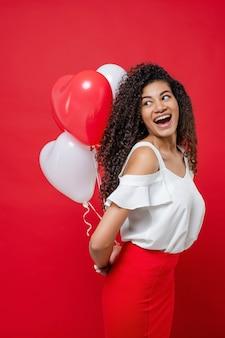 Donna africana abbastanza felice che tiene i palloni variopinti e sorridere dell'elio isolati su rosso