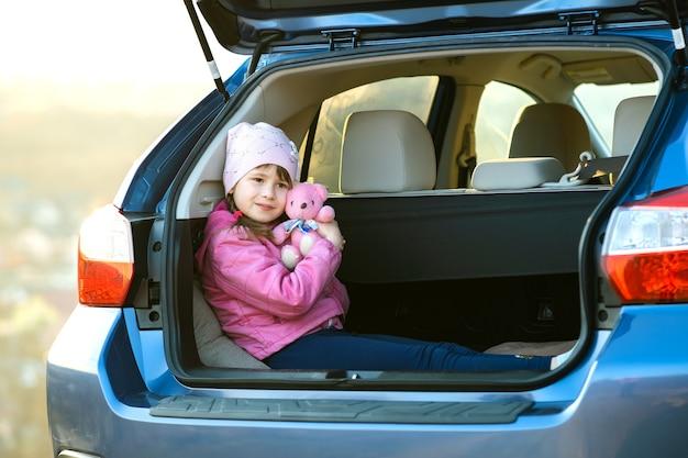 Ragazza abbastanza felice del bambino che gioca con un orsacchiotto rosa del giocattolo in un bagagliaio di un'auto.