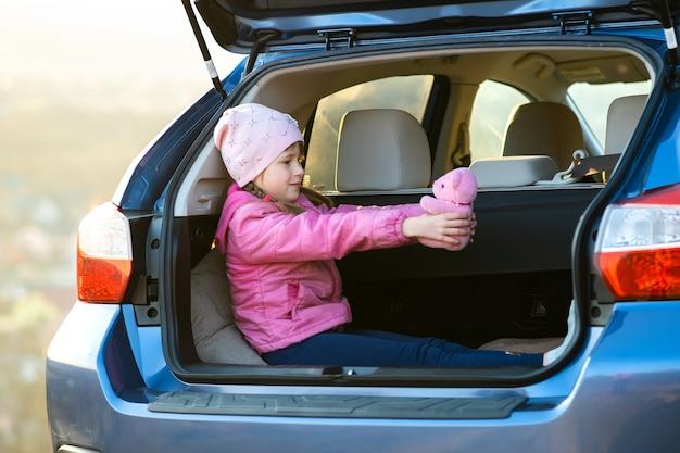 Bambina abbastanza felice che gioca con un orsacchiotto giocattolo rosa nel bagagliaio di un'auto.