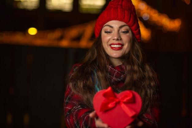 Donna abbastanza felice che tiene una confezione regalo rossa di san valentino con un fiocco su uno sfondo di luci sfocate. spazio vuoto