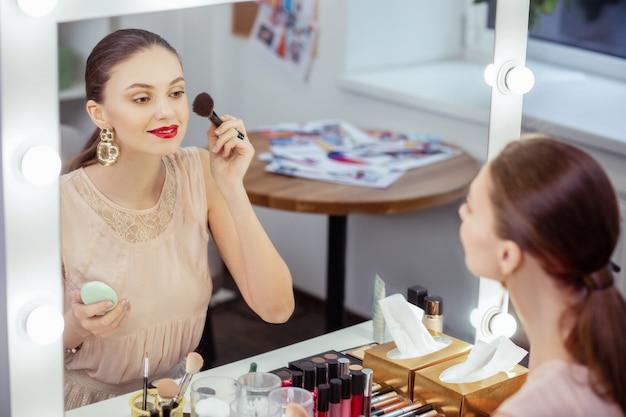 Donna abbastanza felice che guarda il suo riflesso nello specchio