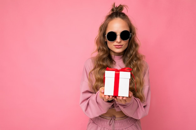 Piuttosto felice giovane bionda donna riccia isolata su sfondo rosa muro indossando abiti sportivi rosa