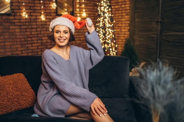 Giovane brunetta abbastanza felice in cappello di natale che si siede sul divano a casa.