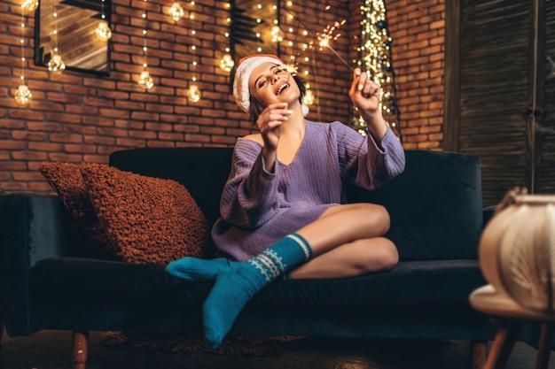 Giovane brunetta abbastanza felice in cappello di natale con lo sparkler nelle mani.