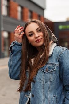 La giovane donna abbastanza felice in giacca di jeans blu vintage cammina all'aperto. elegante modella bella ragazza in posa in città. capispalla di tendenza giovanile per la primavera per le donne. stile casual.