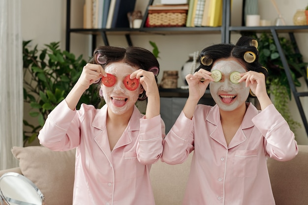 Giovani donne abbastanza felici con maschera di argilla che fanno facce buffe con fette di pomodoro e cetriolo e...