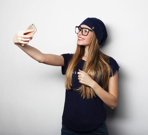 Ragazza graziosa hipster che prende selfie