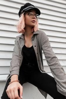Bella donna modello hipster con occhiali alla moda e un berretto alla moda in abiti di jeans con una camicia a quadri si siede vicino a una parete di legno