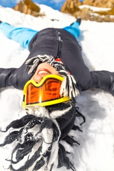 Bella donna hipster sdraiata sulla neve in montagna o in cima alla collina in una giornata di sole con cielo blu e grande roccia