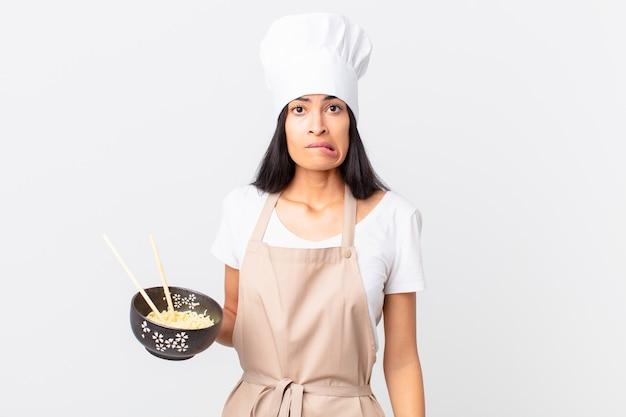Bella donna chef ispanica che sembra perplessa e confusa e tiene in mano una ciotola di noodle