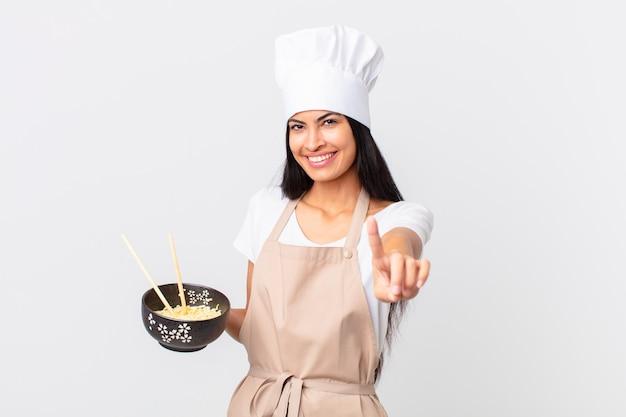 Donna chef piuttosto ispanica che sorride con orgoglio e sicurezza facendo il numero uno e tenendo in mano una ciotola di noodle