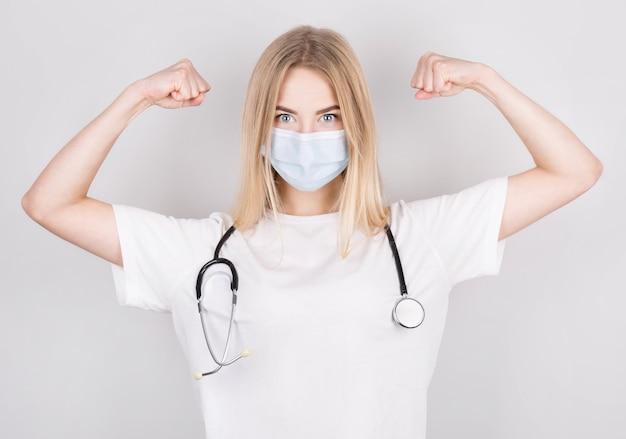 Una dottoressa piuttosto ispanica indossa una maschera, si strofina e flette le braccia, comportandosi come un supereroe