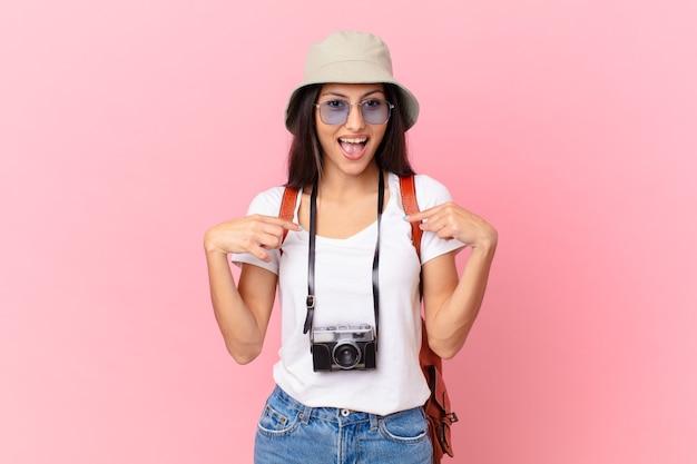 Turista abbastanza ispanico che si sente felice e indica se stesso con un eccitato con una macchina fotografica e un cappello