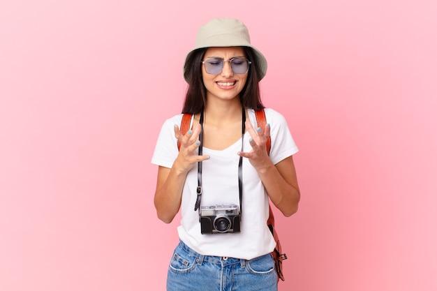 Turista piuttosto ispanico che sembra disperato, frustrato e stressato con una macchina fotografica e un cappello