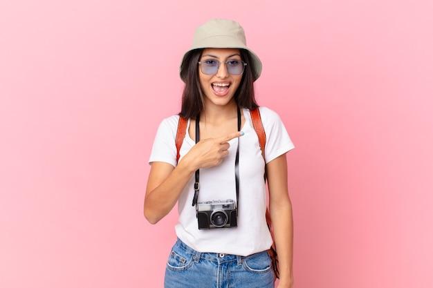 Turista abbastanza ispanico che sembra eccitato e sorpreso che indica il lato con una macchina fotografica e un cappello