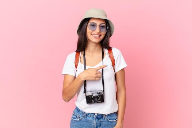 Turista piuttosto ispanico che sorride allegramente, si sente felice e indica il lato con una macchina fotografica e un cappello