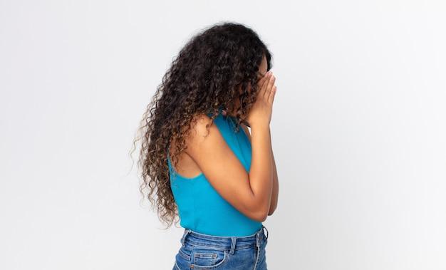 Bella donna ispanica che copre gli occhi con le mani con uno sguardo triste e frustrato di disperazione, pianto, vista laterale